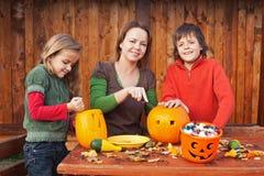 Familia que talla las linternas de la calabaza para Halloween Foto de archivo