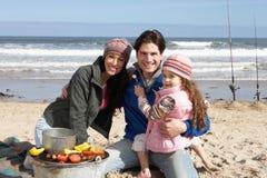 Familia que tiene barbacoa en la playa del invierno Imagen de archivo libre de regalías