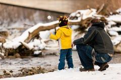 Familia que tiene caminata del invierno en el río Imagen de archivo libre de regalías