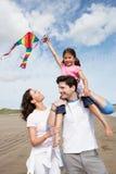 Familia que tiene cometa del vuelo de la diversión el día de fiesta de la playa Imágenes de archivo libres de regalías