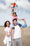 Familia que tiene cometa del vuelo de la diversión el día de fiesta de la playa Imagen de archivo libre de regalías