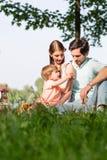 Familia que tiene comida campestre en el lago que se sienta en prado Fotos de archivo libres de regalías