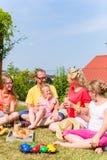 Familia que tiene comida campestre en frente del jardín de su hogar fotos de archivo libres de regalías