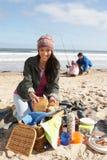 Familia que tiene comida campestre en la playa del invierno Fotografía de archivo libre de regalías