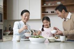 Familia que tiene comida con los palillos en cocina Foto de archivo
