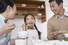 Familia que tiene comida con los palillos en cocina Fotos de archivo
