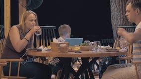 Familia que tiene comida en café al aire libre almacen de video
