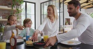 Familia que tiene comida en la mesa de comedor en cocina en el hogar cómodo 4k almacen de video