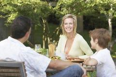 Familia que tiene comida en la mesa de picnic Foto de archivo