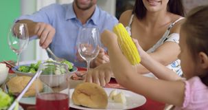 Familia que tiene comida junto en la tabla dinning en casa 4k almacen de metraje de vídeo