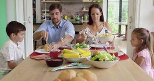 Familia que tiene comida junto en la tabla dinning en casa 4k metrajes