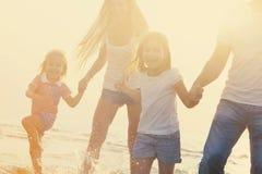 Familia que tiene ing del 'del runÑ de la diversión en la playa en la puesta del sol Foto de archivo libre de regalías