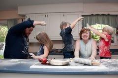 Familia que tiene lucha de la comida en cocina Fotos de archivo