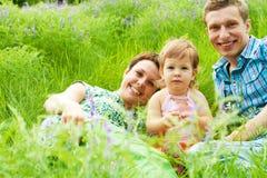 Familia que tiene resto en hierba Foto de archivo libre de regalías