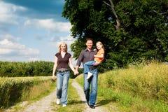 Familia que tiene un niño que lleva de la caminata Foto de archivo libre de regalías