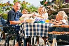 Familia que tiene un partido de la barbacoa Foto de archivo libre de regalías