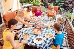 Familia que tiene una fiesta de jardín que come en la tabla fotos de archivo