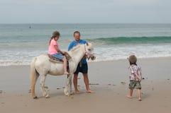 Familia que tiene una lección de montar a caballo en una playa Fotografía de archivo libre de regalías