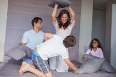 Familia que tiene una lucha de almohada en la cama Imágenes de archivo libres de regalías