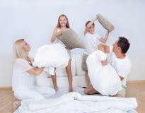 Familia que tiene una lucha de almohadilla junto en cama Fotos de archivo