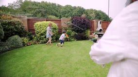 Familia que tiene una lucha del agua en el jardín almacen de video