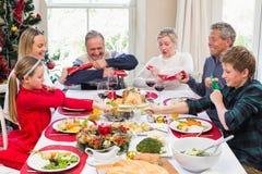 Familia que tira de las galletas de la Navidad en la tabla de cena Fotos de archivo libres de regalías