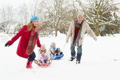 Familia que tira del trineo a través de nieve Fotografía de archivo libre de regalías