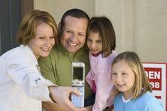Familia que toma el autorretrato en Front Of New House Fotografía de archivo