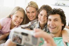 Familia que toma el retrato de uno mismo con las cámaras digitales
