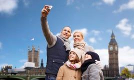 Familia que toma el selfie por la cámara sobre la ciudad de Londres fotos de archivo libres de regalías