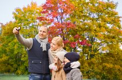 Familia que toma el selfie por smartphone en parque del otoño fotografía de archivo