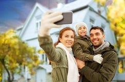 Familia que toma el selfie sobre casa en otoño fotografía de archivo libre de regalías