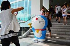Familia que toma las fotos con la figura de Doraemon Imagen de archivo