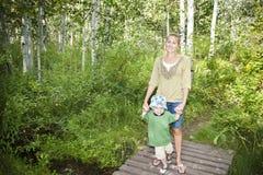 Familia que toma una caminata en las maderas junto Imagen de archivo