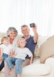 Familia que toma una foto de sí mismos Imagenes de archivo