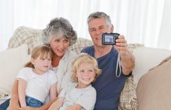 Familia que toma una foto de sí mismos Imagen de archivo libre de regalías