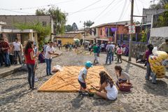 Familia que trabaja en los alfombres, alfombras hechas por el serrín coloreado en las calles cobbled para la procesión San Bartol Foto de archivo