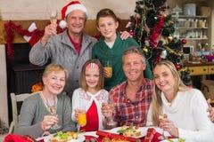 Familia que tuesta con el vino blanco en una cena de la Navidad Fotos de archivo