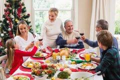 Familia que tuesta con el vino rojo en una cena de la Navidad Fotografía de archivo