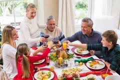 Familia que tuesta con el vino rojo en una cena de la Navidad Fotos de archivo