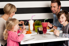 Familia que tuesta los smoothies en restaurante fotos de archivo libres de regalías