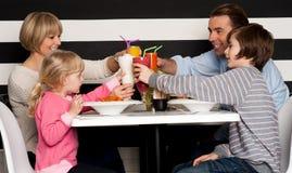 Familia que tuesta los smoothies en restaurante imagen de archivo libre de regalías