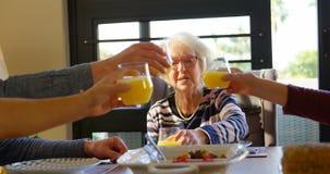 Familia que tuesta los vidrios de jugo en la mesa de comedor en casa 4k metrajes