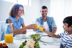 Familia que tuesta los vidrios de zumo de naranja mientras que desayunando Foto de archivo libre de regalías