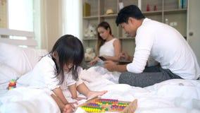 Familia que usa el ordenador portátil y el cuaderno del smartphone en casa