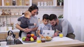 Familia que usa la tableta digital en cocina metrajes