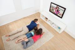 Familia que ve la TV en casa fotos de archivo libres de regalías