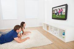 Familia que ve la TV en casa imagen de archivo libre de regalías