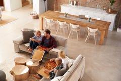Familia que ve la TV y que come la pizza Imágenes de archivo libres de regalías