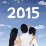 Familia que ve los números 2015 en el cielo Imágenes de archivo libres de regalías